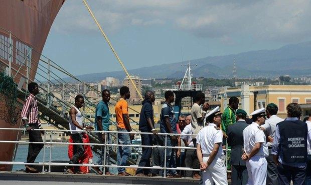 Нелегальные мигранты из Ливии сходят на берег в Италии. Часть беженцев не выжили при перевозке в трюме корабля