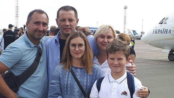 Роман Сущенко ( в центре) в эеропорту