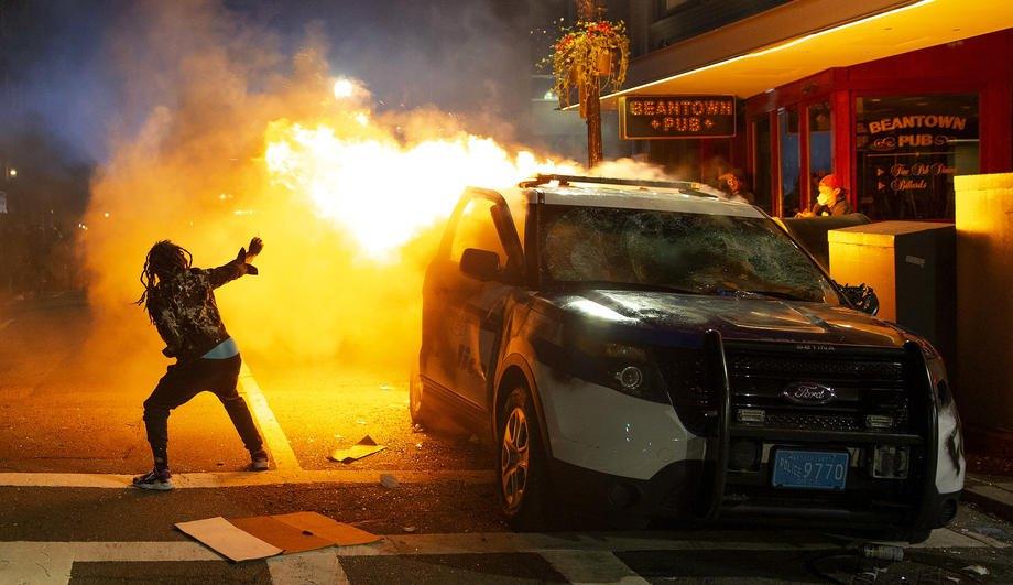 Мужчина пытается зажечь сигарету от пламени горящего полицейского авто во время столкновений в Бостоне, штат Массачусетс, США, 31 мая 2020 года
