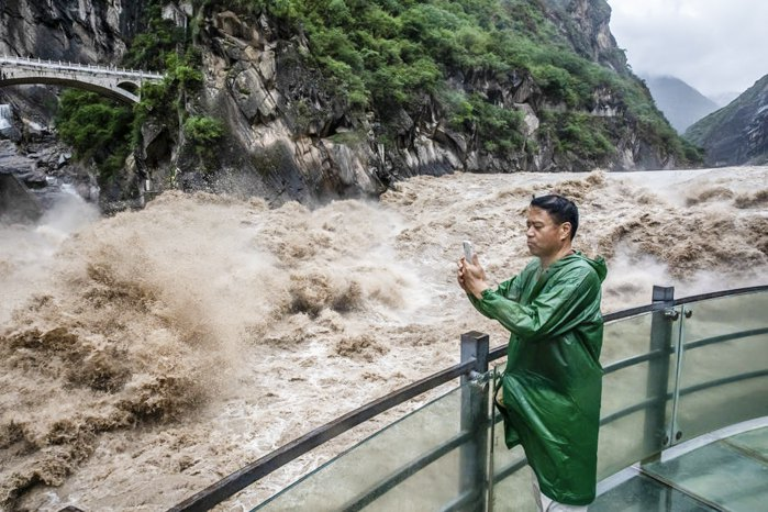Турист делает селфи на фоне каньона на реке Цзиньша, провинция Юньнань, 14 июля 2020 г.