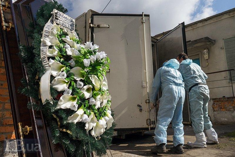 Працівники відчиняють холодильну камеру для зберігання тіл людей померлих від ковіду.
