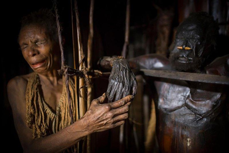 Родственник держит руку мумифицированного Гемтасу во время ритуала.