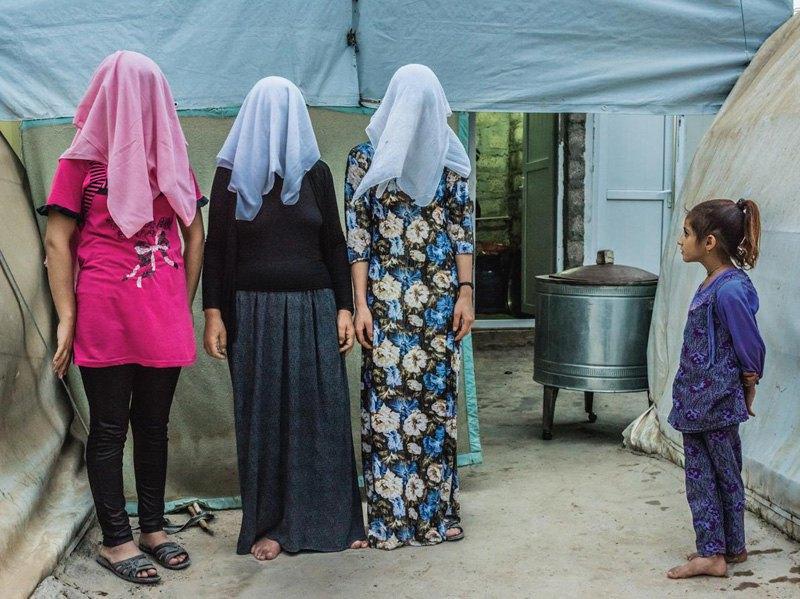 Девочка смотрит, как три курдские женщины фотографируются с прикрытыми лицами в лагере для беженцев. Две из них рассказали, что принудительно вышли замуж за боевиков ИГИЛ прежде, чем бежать сюда.