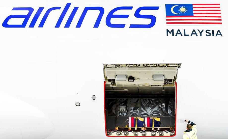 Останки жертв борту MH17 вантажать для перевезення до Малайзії з міжнародного аеропорту Схіпхол, Амстердам, Нідерланди, 21 серпня 2014 р.