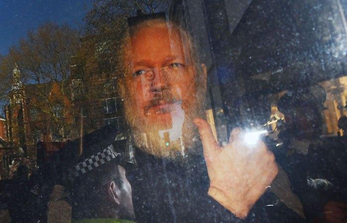 Джулиан Ассанж в автобусе после задержания полицией Лондона.