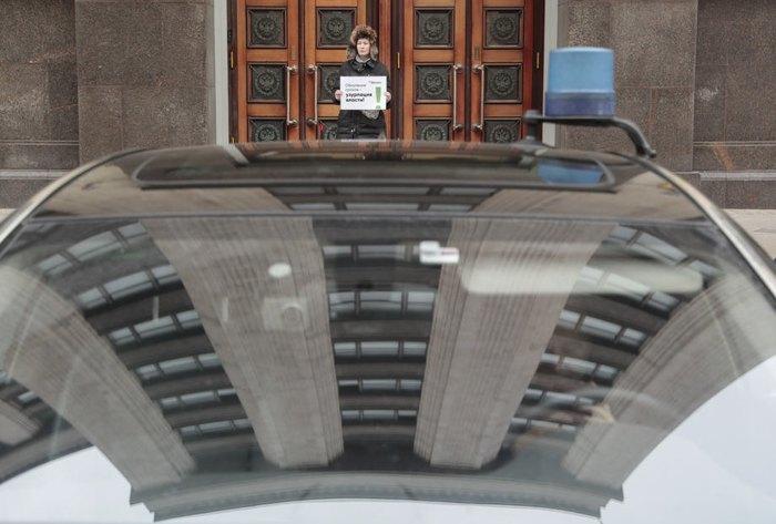 Одинокая активистка с плакатом 'Обнуление президентских сроков - узурпация власти' стоит перед Государственной думой, Москва, 11 марта 2020