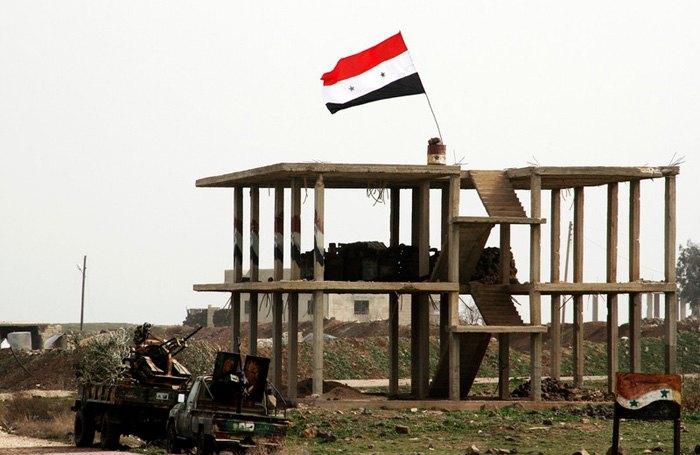 Сирийский флаг на здании в городе Дейр-эль-Адас, провинция Дераа, 11 февраля 2015 .
