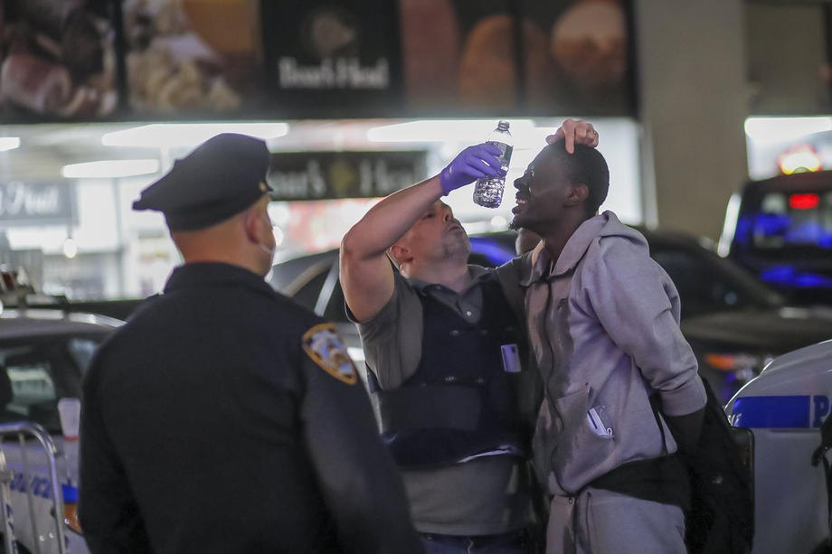 Сотрудники нью-йоркского департамента полиции оказывают помощь задержанному подозреваемому мародеру в Манхэттене ,Нью-Йорк, 01 июня 2020
