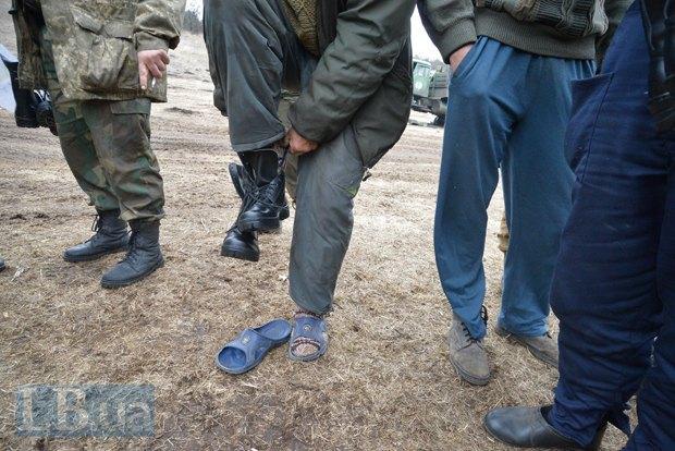 Артиллерист меняет резиновые тапочки на обувь, привезенную волонтерами