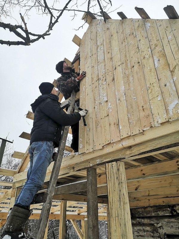 Юрій Ягусевич з Артемом Алєксєєвим покривають дах хати, щоб провести на ділянку світло