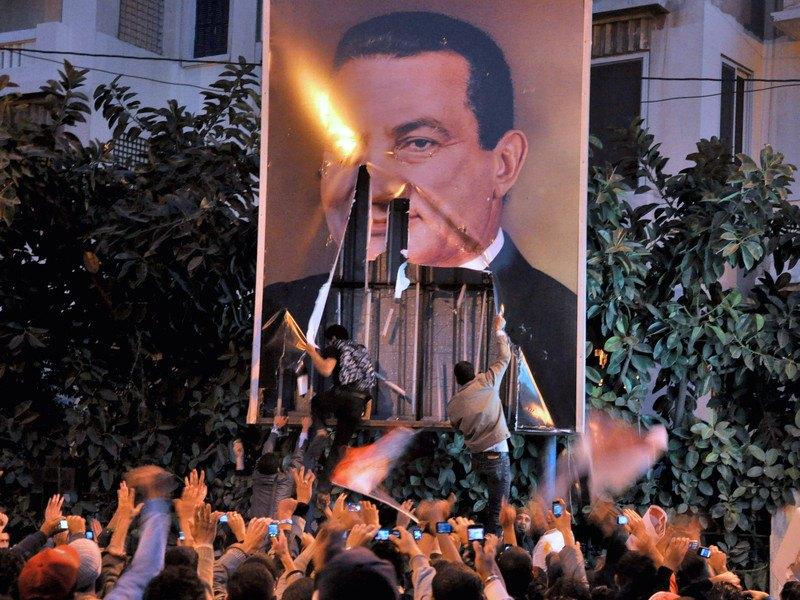 Учасники протесту зривають плакат президента Єгипту Хосні Мубарака під час демонстрації в Олександрії, Єгипет, 25 січня 2011