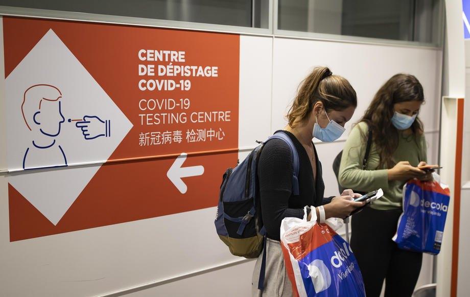 Пасажири біля вказівника пункту санітарного контролю для пасажирів, які прибувають з країн, визначених червоними зонами, в аеропорту Руасі Шарля де Голля поблизу Парижа, 25 квітня 2021 р.