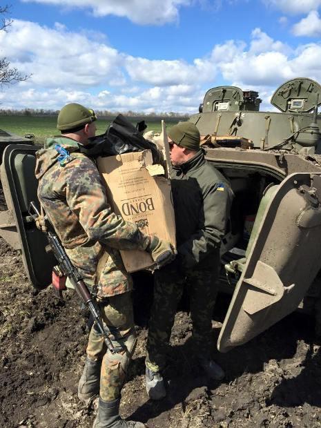 Бойцы загружают волонтерскую помощь в БМП