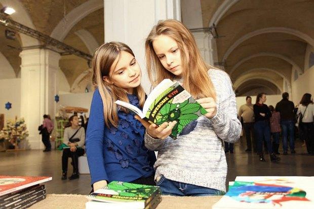 В руках у девочки англоязычный путеводитель Awesome Kyiv издательства <<Основы>>