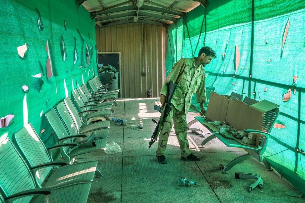 Солдат афганської армії оглядає речі, залишені американськими військовими після відльоту з авіабази Баграм