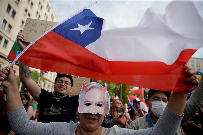Активистка в маске президента Чили Себастьяна Пинеры держит чилийский флаг во время акций протеста в Сантьяго, 26 октября 2019.