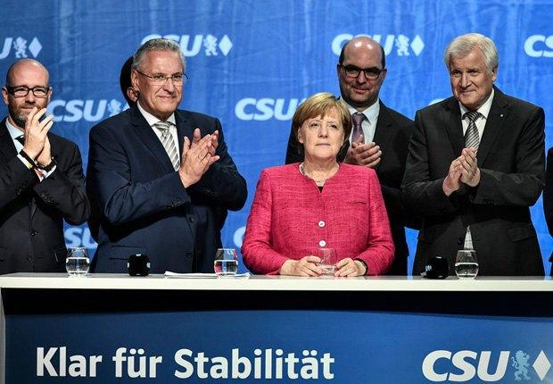 Ангела Меркель в сопровождении Хорста Зеехофера (справа) и министра внутренних дел Баварии Иоахима Херрманна (второй слева) во встречи с избирателями в Мюнхене, 22 сентября 2017 .