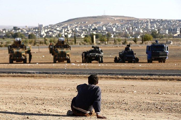 Курд смотрит на турецкий патруль возле турецко-сирийской границы в районе Суруч, Турция.