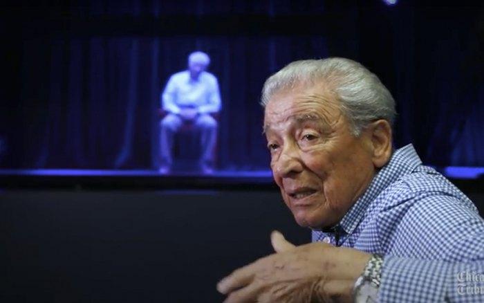 Переживший Холокост Аарон Эльстер на фоне его голограммы в Иллинойском музее и образовательном центре Холокоста
