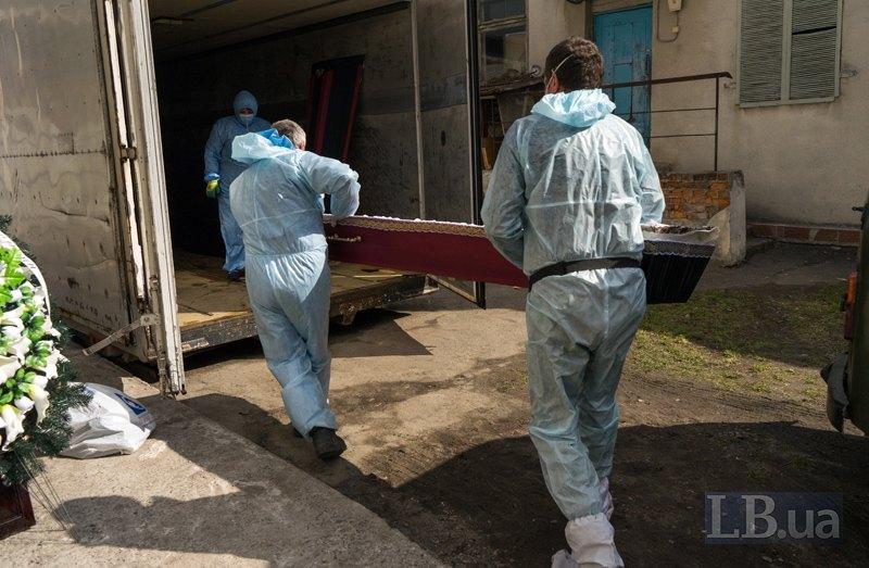 Медпрацівники несуть труну в камеру, де зберігаються тіла ковідних померлих.