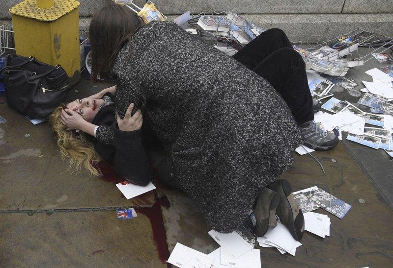 Прохожая помогает женщине, которая пострадала во время теракта в Лондоне.