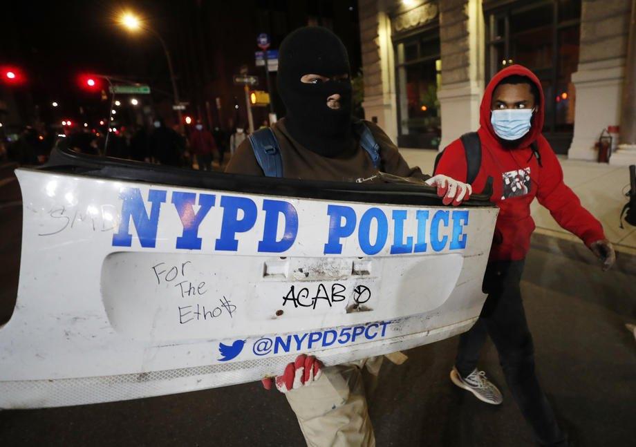 Протестующие несут бампер полицейского автомобиля в Нью-Йорке во время беспорядков,  31 мая 2020