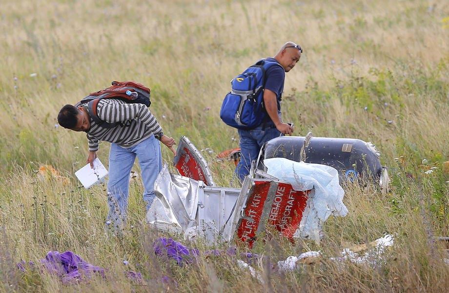 Малайзійські експерти досліджують уламки на місці катастрофи рейсу Boeing 777 Malaysia Airlines MH17 поблизу Грабового, Україна, 22 липня 2014.
