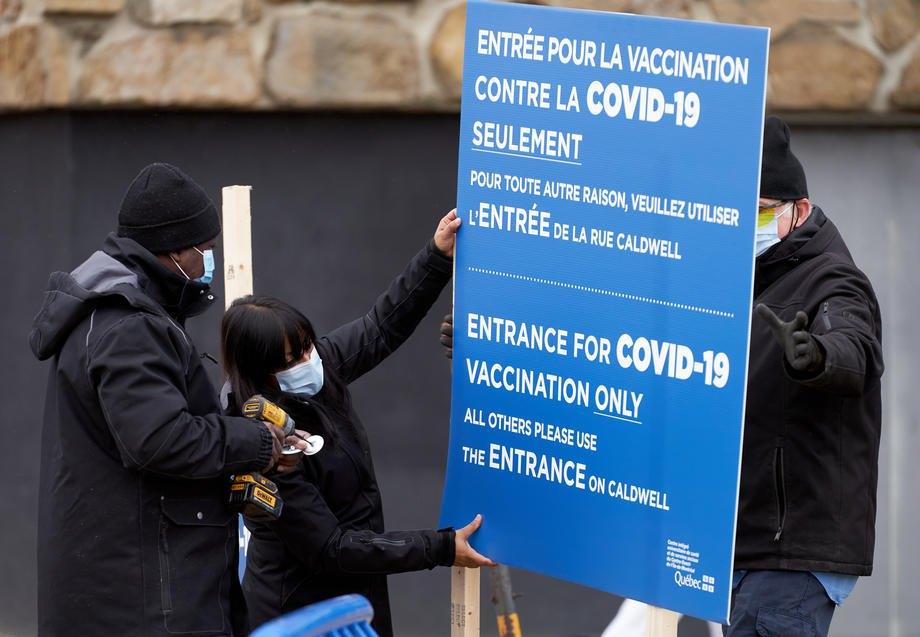 Працівники встановлюють вивіску в першому центрі для вакцинації проти Covid-19 в Монреалі, Канада, 14 грудня 2020 р.
