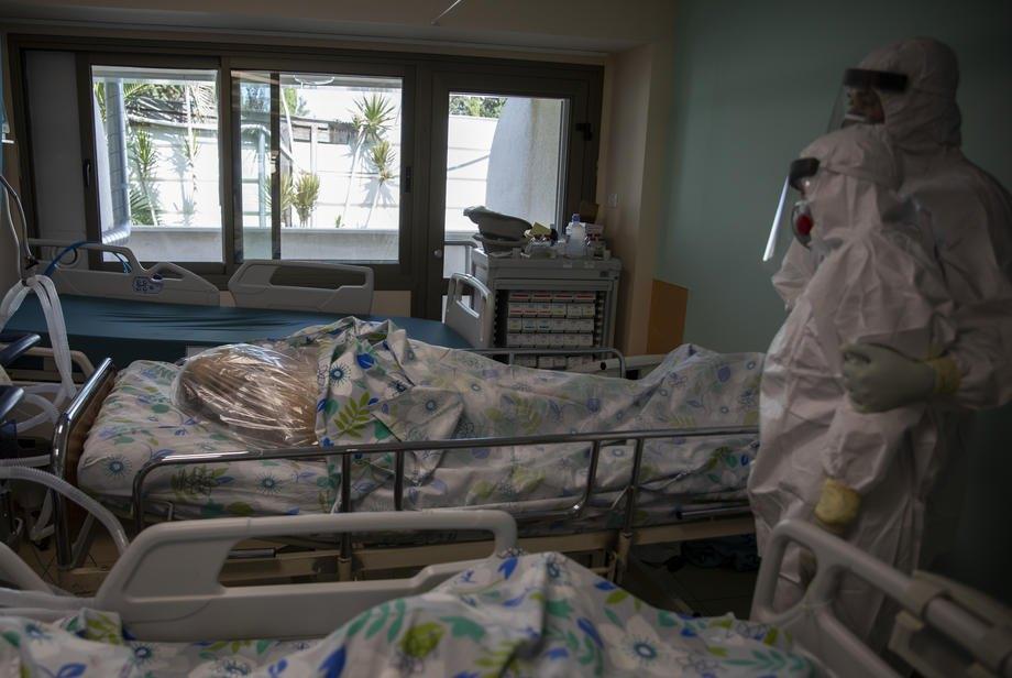 Родичі (у захисних костюмах справа) прощаються з членом родини, котрий помер від ускладнень перебігу COVID-19 в лікарні міста Нагарія, Ізраїль, 01 жовтня 2020
