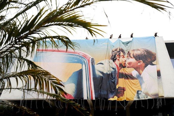 Постер Каннского кинофестиваля вешают на фасад Дворца фестивалей
