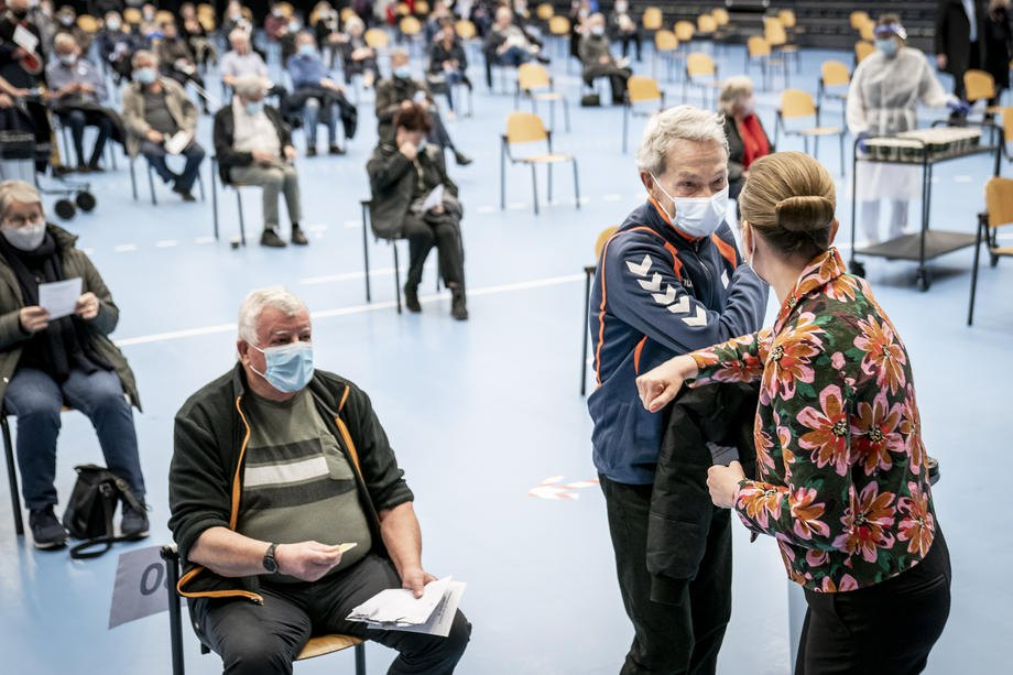 Премьер-министр Дании Метте Фредериксен (спиной ) во время посещения центра вакцинации в Роскилле, 12 апреля 2021 г.