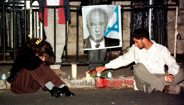 Ізраїльтянин запалює свічку поруч з портретом вбитого ізраїльського прем'єр-міністра Іцхака РабІна.