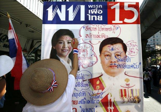 оппозиционеры разрисовывают плакат с фотографией премьера Йинглак Чиннават
