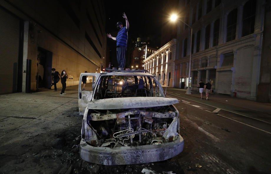 Протестующий стоит на сгоревшей машине Департамента полиции города Нью-Йорка, 30 мая 2020 года
