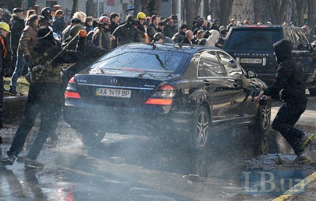 Протестующие бьют стекла автомобиля, который выезжает из офиса ПР