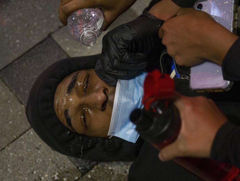 Протестующие помогают мужчине, которого забрызгали перцовым газом во время столкновений с полицией в Бостоне, 31 мая 2020
