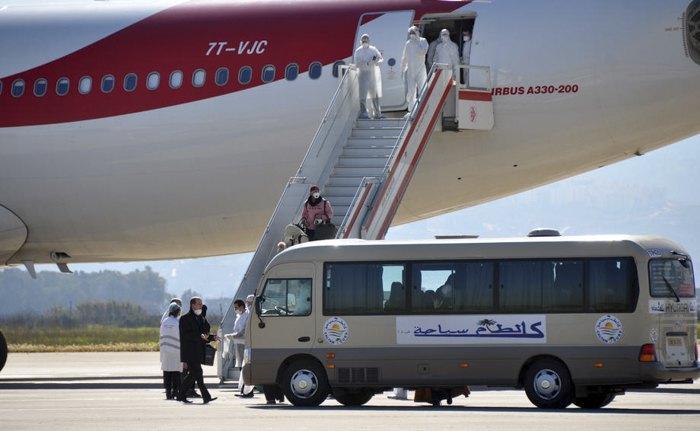 Медперсонал в защитных костюмах встречает алжирцев, ливийцев и мавританцев после их эвакуации из Китая в аэропорту Алжира