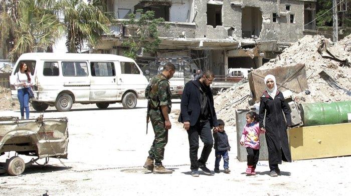 Местные жители в городке Замалка, Восточная Гута, который был недавно захвачен войсками Асада, Сирия, 11 апреля 2018.
