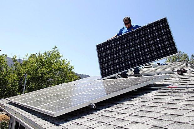 Работник Miracle Solar устанавливает солнечные батареи на доме, штат Калифорния, США, 5 августа 2016 года