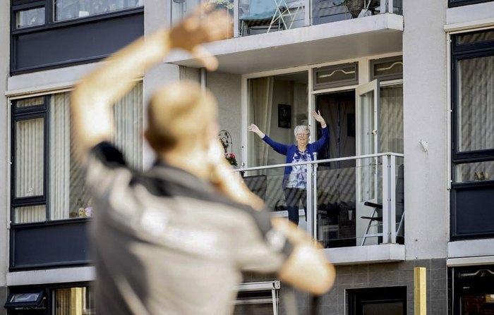 Лiтня жінка робить руханку на своєму балконі, Квінтшеул, Нідерланди, 8 квітня 2020.