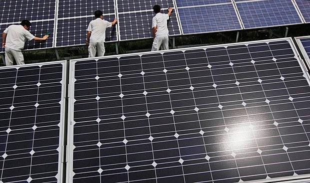 Рабочие чистят солнечные панели на выставке, провинция Хэбэй, Китай