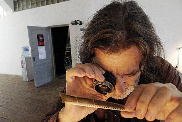 Александр Гляделов смотрит пленку отбырая кадры для печати