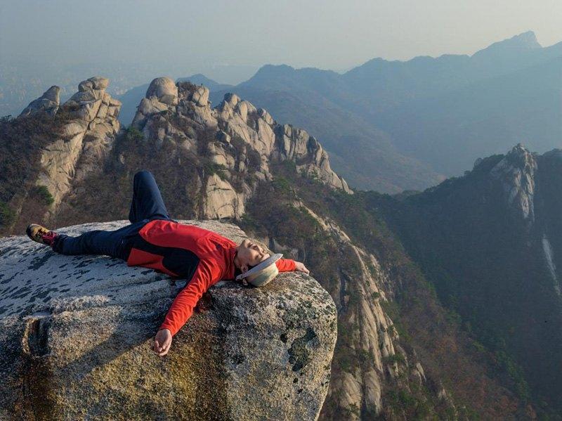 Продавец из Сеула Сунвинь Хуана отдыхает после пешей прогулки по Национальному парку Пукхансан.