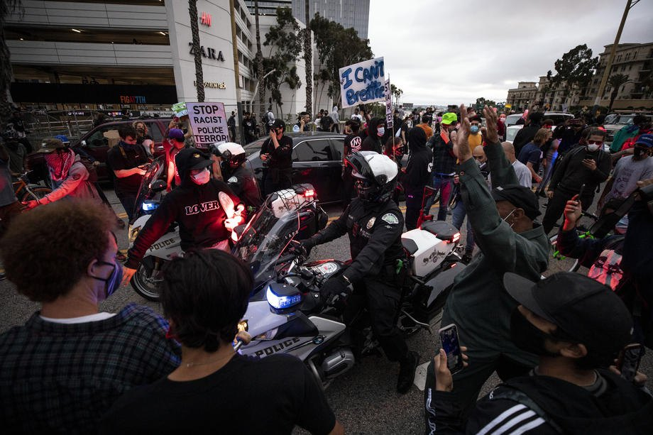 Полицейский на мотоцикле в окружении разъяренных демонстрантов , Лос-Анджелес, 29 мая 2020
