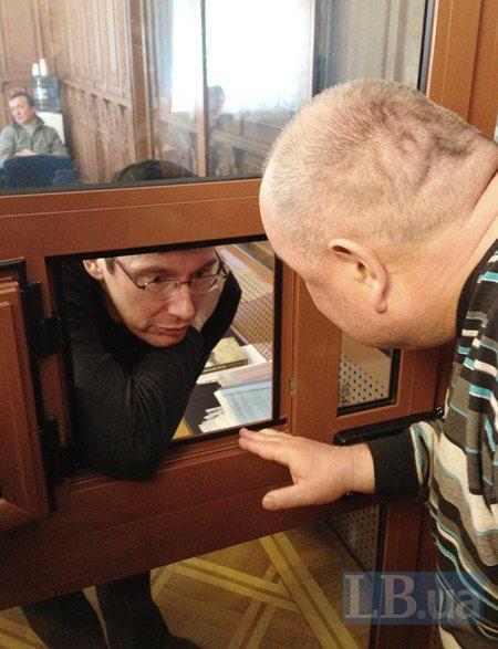 """Луценко находится в стеклянном """"аквариуме"""", для того чтобы быть услышанным в зале, ему, говоря, необходимо наклоняться к форточке в этом аквариуме."""