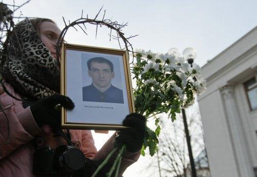 Активистка держит портрет Владимира Чаплинского во время акции