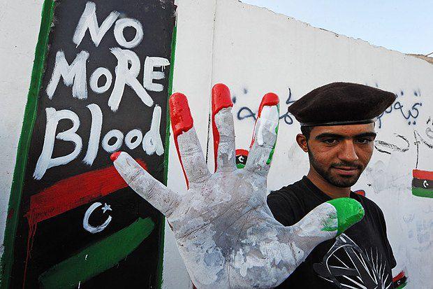 Август 2011. После захвата Триполи ливиец показывает цвета ливийского флага-триколора, который позднее стал официальным знаменем Национального переходного совета