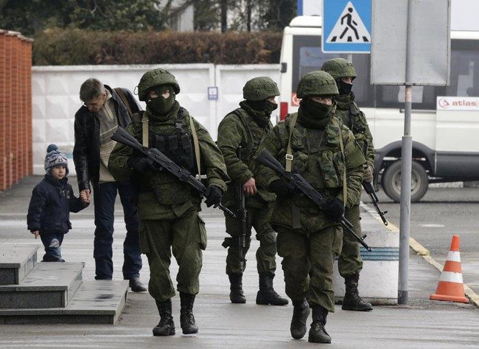 Неопознанные вооруженные люди в военной форме охраняют здание возле аэропорта в Симферополе, Крым, 28 февраля 2014.