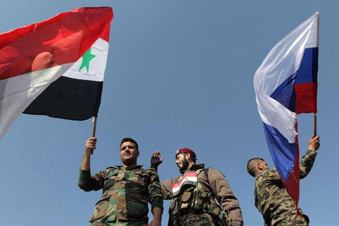 Сирийские солдаты с национальным флагом и флагом России на акции в поддержку правительству на площади Омейяд в Дамаске, Сирия, 14 апреля 2018.