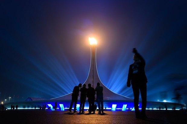 Люди фотографируются возле олимпийского огня вечером 16 января